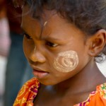 Burmese girl from refugee camp whose face is decorated with the yellow face paint the Burmese use as a sun protector and a beauty product.